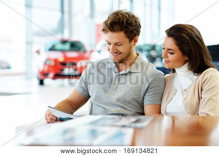 Beautiful young couple reading a booklet at the dealership showroom.