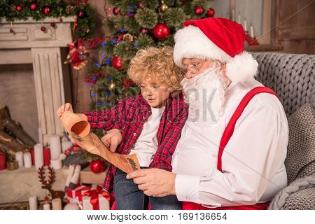 Happy Santa Claus and child on his knee reading Christmas wishlist