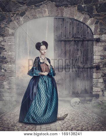 Beautiful woman in medieval dress with book standing near old gate