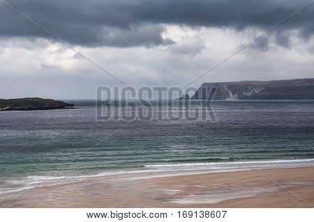 North Coast Scotland - June 6 2012: Huge cliffs tower over Durness Beach a sandy patch looking north on a rough coast among rock cliffs and sprinkled pieces of rock.