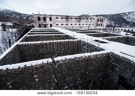 Exterior of buildings of old decayed abandoned prison in Kolyma
