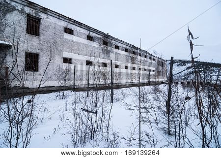 Exterior of housing of old decayed abandoned prison in Kolyma in sunlight
