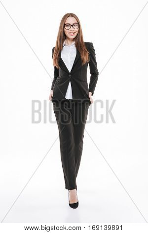 Full length portrait of a confident young woman in formalwear and eyeglasses walking and smiling isolated on white