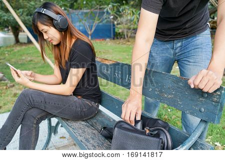 Thief trying to steal the wallet in the bag while woman using mobile phone and listening to music on sofa in the park