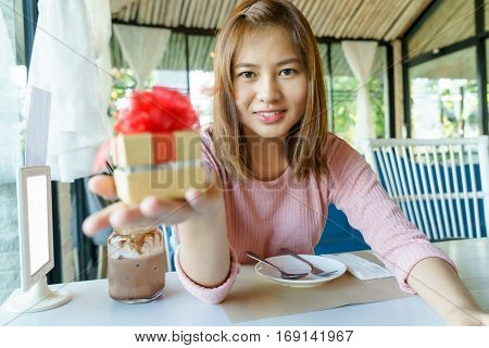 Smile young woman giving a golden present box with red ribbon to her lover in restaurant