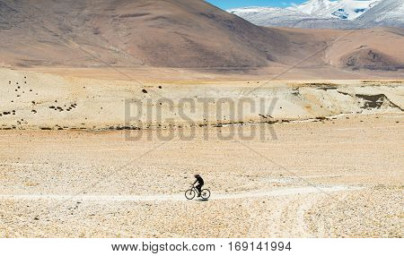 young man cycling through the remote area on rugged road in the himalaya rangemotion blur soft focus