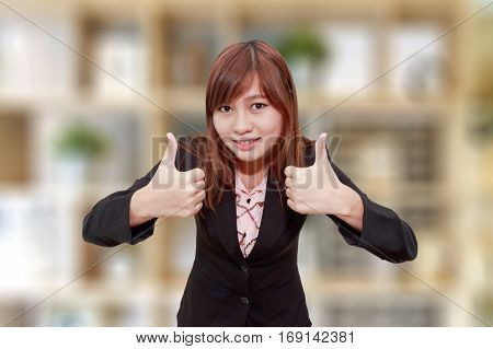 Smiling businesswoman holding thumps up on blurred background