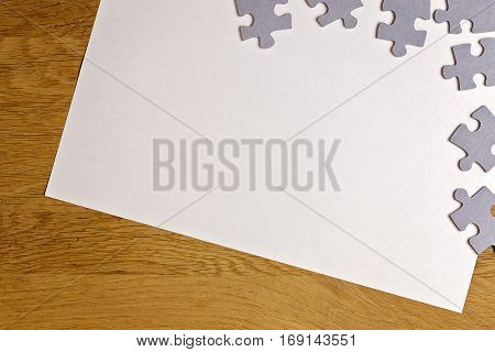 Blank white paper piece with puzzle pieces on wooden background. Top view. Copy space for text. Toned