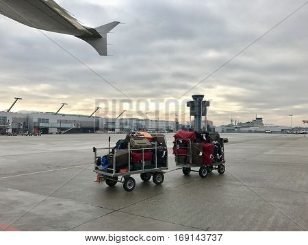 Passenger luggage on a trailer next to a commercial airline jet aircraft at the airport