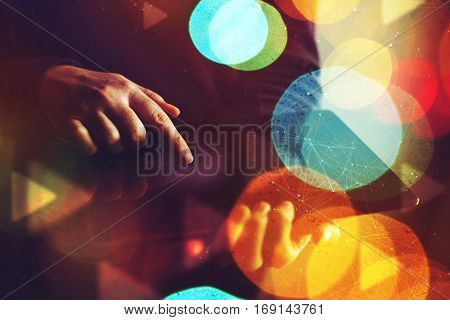Close up of female hands using digital tablet computer abstract low key composition with colorful bokeh light