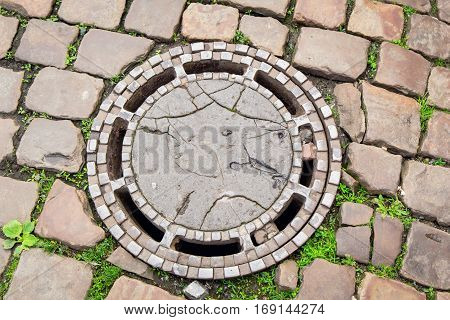Old metal sewer cover on paving stones road