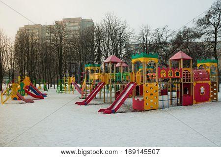 deserted playground in snow winter light day