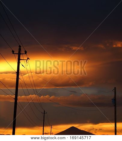 Sky and clouds lit up with a golden glow after a heavy rain storm at sunset over Black Butte and roadside power lines in Central Oregon on a summer evening.