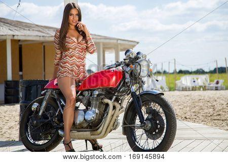 Biker Girl on Retro Motorcycle - Portrait of a cool woman on a vintage motorbike