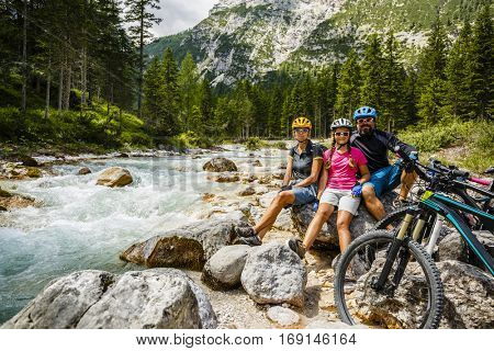 Family bike rides in the mountains while relaxing on the riverbank.