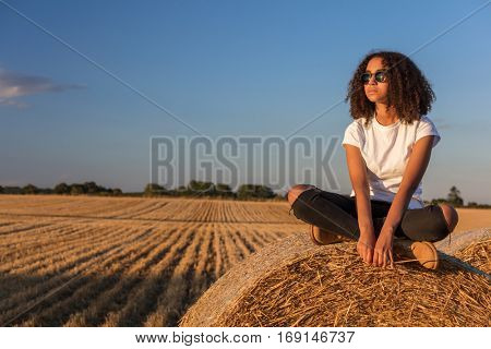 A beautiful and thoughtful mixed race African American female girl child teenager young woman in sunshine wearing sunglasses and sitting on a hay bale in a field