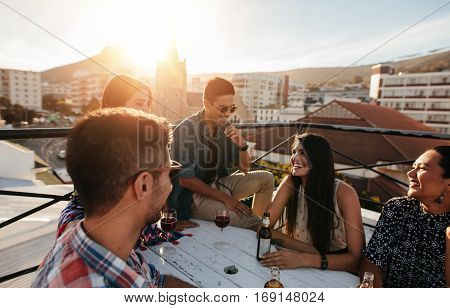 Group of friends having a party on the rooftop. Young men and women sitting around table with drinks and laughing.