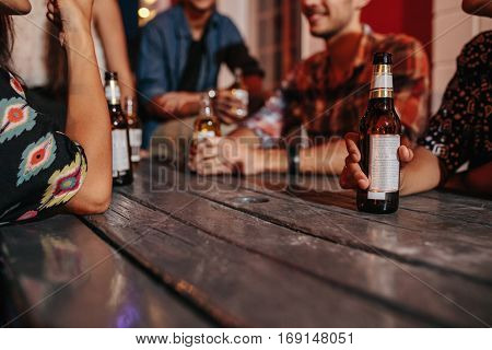 Group of friends sitting around a table having drinks. Focus on beer bottle in hand of a woman sitting with friend. Young people having rooftop party.
