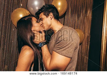 Shot of romantic young couple kissing in the night club. Man and woman in the pub.