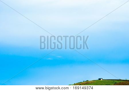 Lonely farmhouse and blue sky in evergreen hill with copy space.