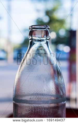 A necks of clear glass bottles in the sunlight