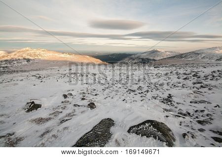winter sunset over a mountain top and snow plateau