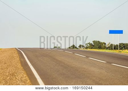 Countryside asphalt road with markings and blank signpost to copy space. Background with limited depth of field.