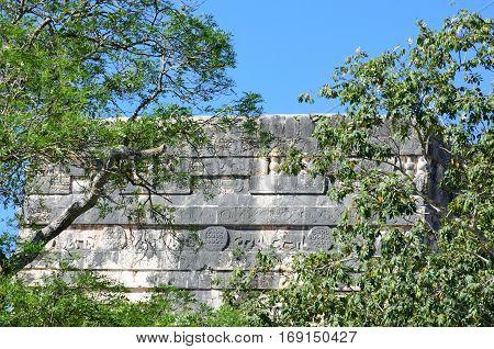 Mayan stone construction half hidden by trees