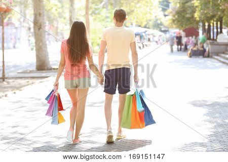 Happy couple walking back with colorful bags walking back outdoors