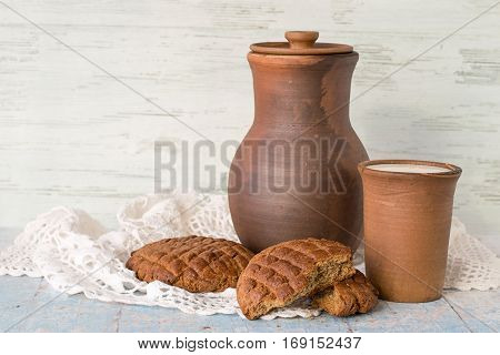Breakfast. Milk in a clay jug and fresh scones made from rye flour on white of openwork napkin on old wooden table.