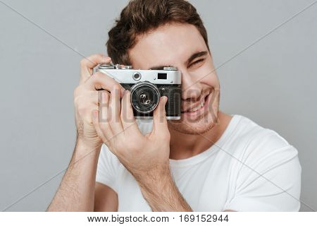 Close up portrait of Smiling Man making photo on retro camera in studio. Isolated gray background