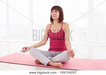 Mid shot of slim woman doing yoga. Sitting in lotus position in lotus position. Woman practicing yoga in the sport gym