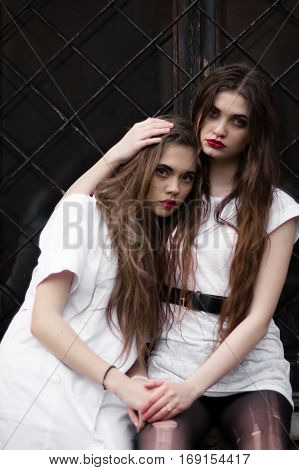 Two mentally sick sisters in strange dark hospital. Picture of two beautiful scared frightened girls in white clothes on black background. Halloween party. No feelings, no emotions. Wild girls. Demon.