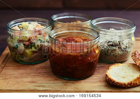 Close-up of a collection of salads in jars. Different jars standing on the wooden cutting board