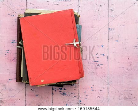 stack of retro folders on old pink wooden background.