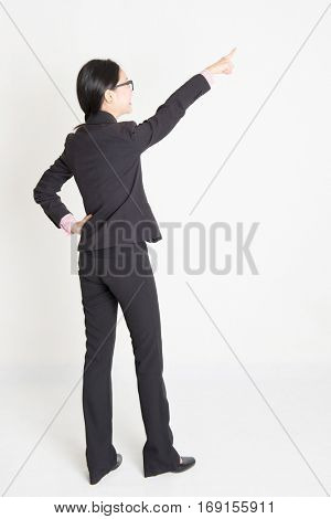 Full body rear view of young Asian businesswoman in formalwear finger pointing on something, standing on plain background.