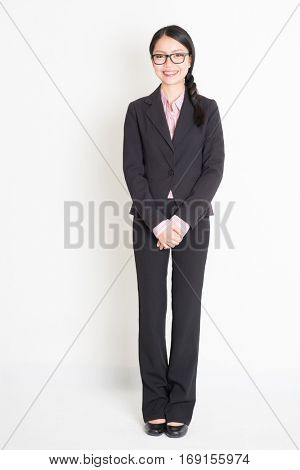 Full body portrait of young Asian businesswoman in formalwear smiling, standing on plain background.