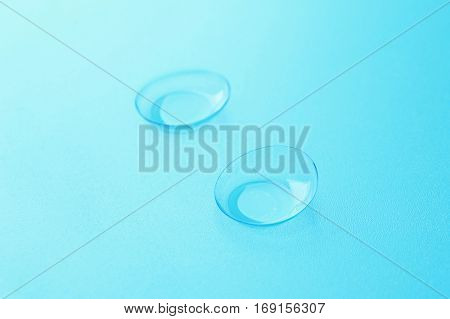 Pair of contact lenses on blue background, close up view