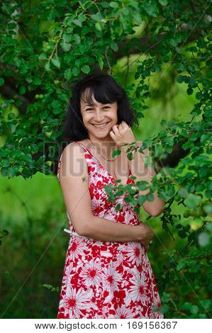 Happy girl laughing against a green trees background. Concept of joy.Smiling happy woman. Happy cheerful smiling brunette woman with unreally beautiful healthy white pretty smile. Good and happy life.