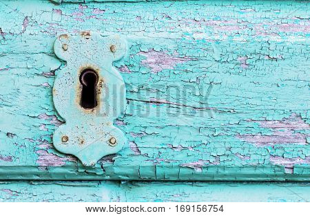 Beautiful old vintage rustic cracked turquoise paint wooden door and rusty iron lock and keyhole as a background
