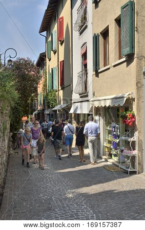 SIRMIONE, ITALY - AUGUST 7, 2014: People at a charming street in the village of Sirmione on lake Garda Italy.