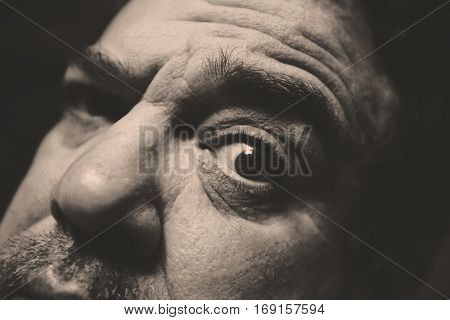 Creative black and white monochrome portrait of man with eyes wide open. Close-up.