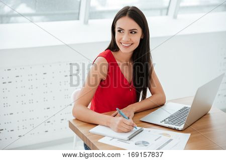 Smiling business woman in red shirt sitting and writing something by the table as well as looking away