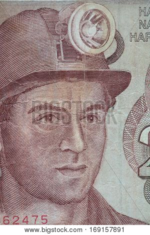 worker in a helmet with a lantern portrait on a banknote
