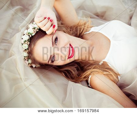 Portrait of a beautiful fashion bride, sweet and sensual. Wedding make up and hair. Flowers background. Art modern style. Blue eyes. Picture of happy cheerful smiling girl with big white healthy smile