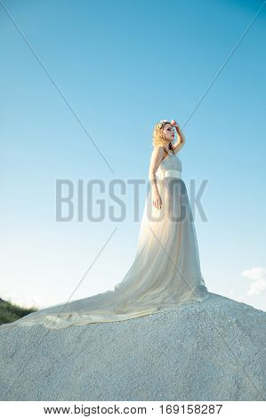 Beautiful girl in long white unusual dress with loop look aside. Beautiful girl in long white dress stand on mountains on blue bright sky background. Pretty girl on sky fly.