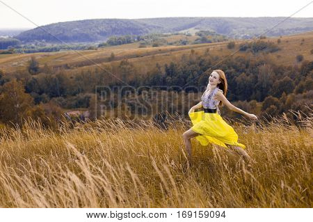 Happy playful young pretty girl running on the field with green, yellow wheat on the way to good life.Happy adventure in summer, summertime.Cheerful smiling girl in light yellow dress running on field