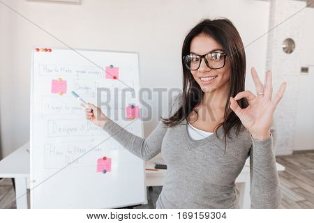 Photo of young cheerful businesswoman in office working with flipchart. Look at camera while making Okay gesture.