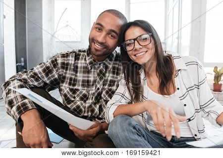 Picture of cheerful business partners in office working with documents on floor. Look at camera.