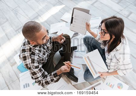 Top view picture of young cheerful business partners in office working with documents on floor.